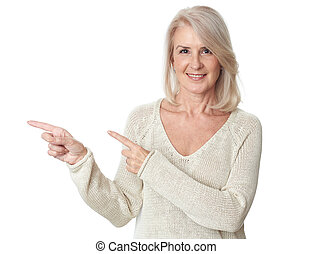 elegant 50 years old woman pointing at white background