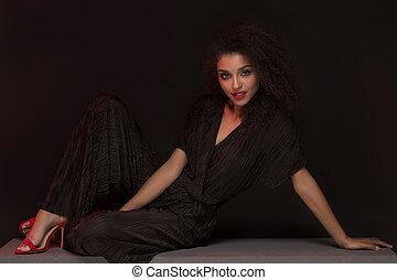Elegant afro woman posing in red high heels.