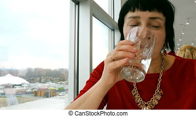 Elegant aged woman, caucasian ethnicity, drinks water from...