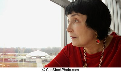 Elegant aged woman, caucasian ethnicity, looking to window....
