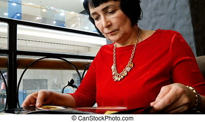 Elegant aged woman in red dress, caucasian ethnicity, reads...