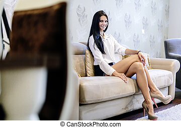 Elegant and sexy woman sitting on a sofa in a luxurious room