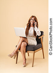 Elegant attractive middle aged woman sitting in a chair