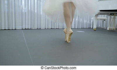 Elegant ballerina dances in ballet school indoors.