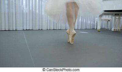 Elegant ballerina dances in ballet school indoors. Young...