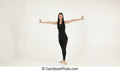 Elegant ballet dancer stretching on white background....