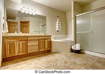 Elegant bathroom in soft tones with hardwood cabinets and marble tiled floor.