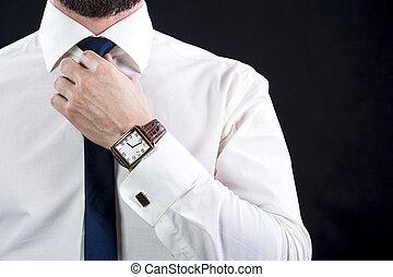 Elegant bearded man tying up his necktie