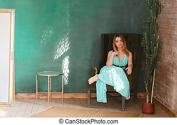 Elegant beautiful woman wearing classic dress sitting in loft interior with wooden floor and brick wall. Big green empty wall for text.
