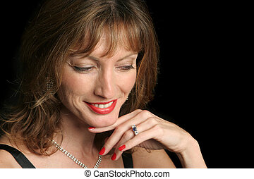 A beautiful woman in an evening gown and diamonds, amused. Black background.