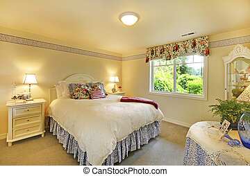 Elegant bedroom interior with white bedding and beige walls.