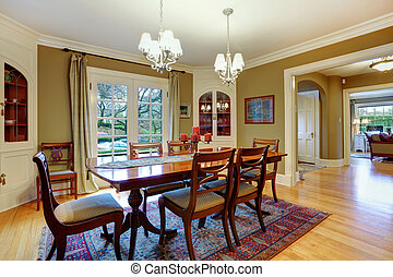 Elegant big dining room with khaki walls, hardwood floor, cherry wooden dining table set, and rustic cabinets