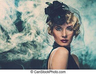 Elegant blond retro woman wearing little hat with veil in...