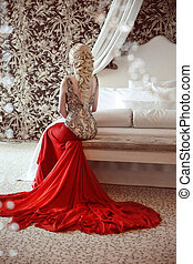 Elegant blond woman model wearing in luxurious red gown with...