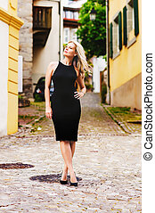 Elegant blond young woman posing outdoors wearing slim black dress and high heel shoes