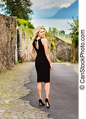 Elegant blond young woman posing outdoors wearing small black dress and high heel shoes
