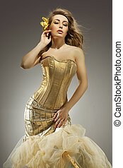 Elegant blonde beauty posing in a golden dress