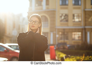 Elegant blonde girl with long hair wearing coat, posing in sun glare. Empty space