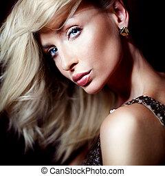 Elegant blonde lady looking at camera.