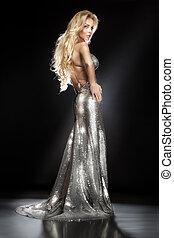 Elegant blonde lady posing in silver long evening dress.