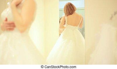 Elegant bride trying wedding gown in bridal shop in fitting...