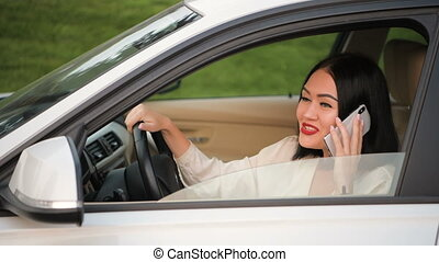 Elegant brunette business woman sitting at the wheel of a car talking on the phone