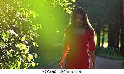 Elegant brunette girl in red dress walking along sunny park alley. Slow motion video, 120 fps