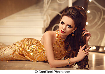 Elegant brunette sexy woman in golden dress lying on the floor by mirror with bulbs. Fashion expensive gold jewelry. Beauty makeup. Hairstyle.