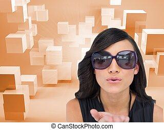 Elegant brunette wearing sunglasses sending kiss to camera
