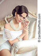 Elegant brunette woman portrait. Retro lady with fashion pearls