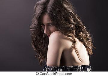 Elegant brunette woman with naked shoulders
