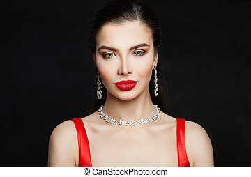 Elegant brunette woman with red lips makeup and diamond necklace and earrings on black background