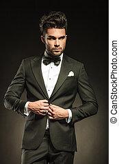 Elegant business man arranging his tuxedo while looking away...