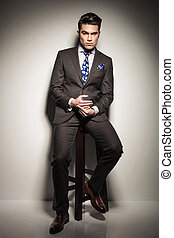 elegant business man sitting on a stool, thinking. - Full...