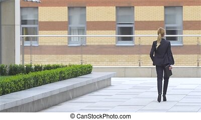 elegant business woman with tablet computer goes around office building. slow motion