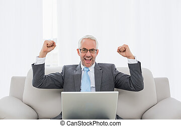 Elegant businessman cheering with laptop at home - Elegant...