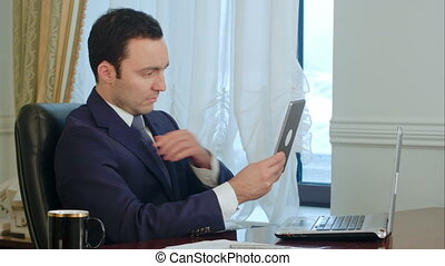 Elegant businessman correcting his suit jacket and hair looking at modern tablet