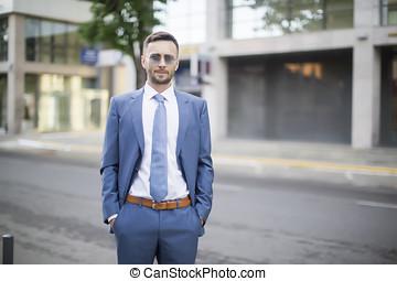 elegant businessman in blue suit walking down the street