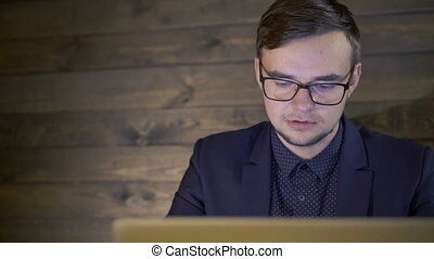 Elegant businessman sitting in cafe and using a laptop