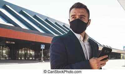 Elegant businessman wearing protective mask in airport. ...