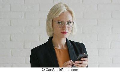 Elegant businesswoman browsing smartphone - Beautiful young...
