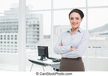 Elegant businesswoman smiling with arms crossed in office