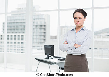 Elegant businesswoman standing with arms crossed in office