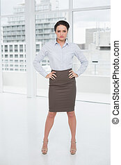 Elegant businesswoman standing with hands on hips in office