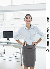 Elegant businesswoman with hands on hips in office