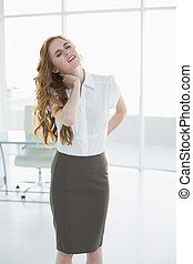 Elegant businesswoman with neck pain in office