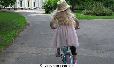 Elegant child girl with hat and pink dress riding a bike in...