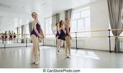 Elegant children ballet dancers are practising arms...
