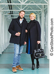 Elegant couple dressed in coat standing at lobby