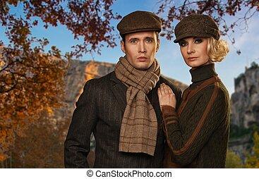 Elegant couple in caps against autumnal landscape